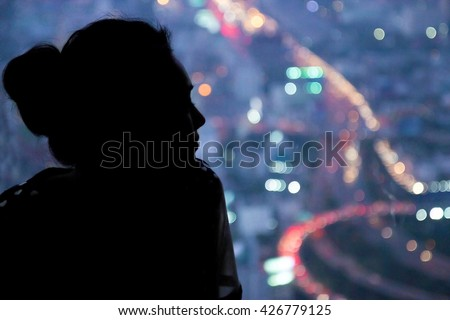 Young woman watching the view from skyscraper. Contours of the woman to background night city. Black woman silhouette in the window of a skyscraper. Dark outline woman watching traffic night city. - stock photo