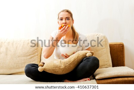 Young woman watching TV and eating chips - stock photo