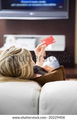 Young woman watching tv and using credit card - stock photo