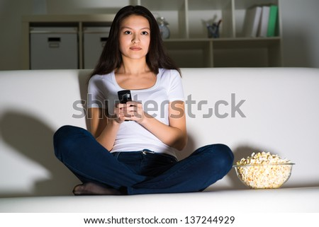 Young woman watching TV on the couch, eating popcorn - stock photo
