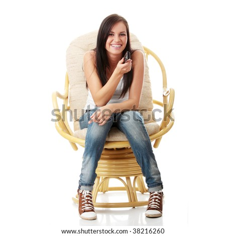 Young woman watching TV with remote control in hand while sitting on armchair isolated - view from TV - Change the channel concept - stock photo