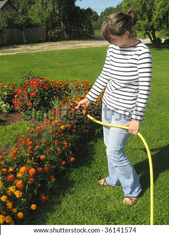 Young woman, watering the flowers in the yard - stock photo