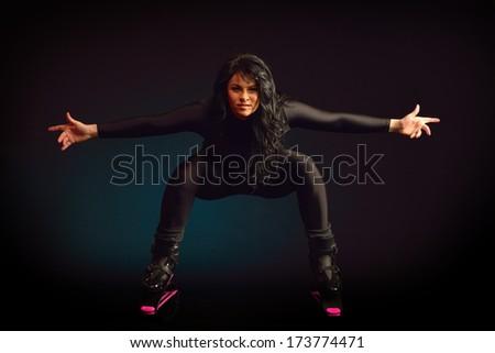 young woman weaaring kangoo jumps indoors - stock photo