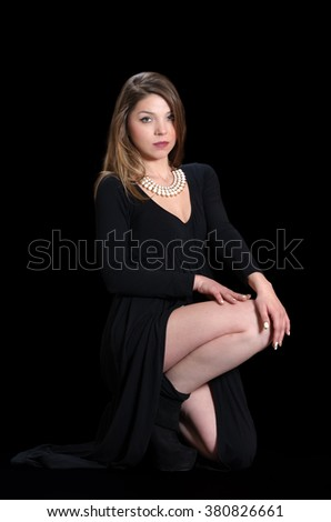 Young woman wear long black dress and necklace against black background