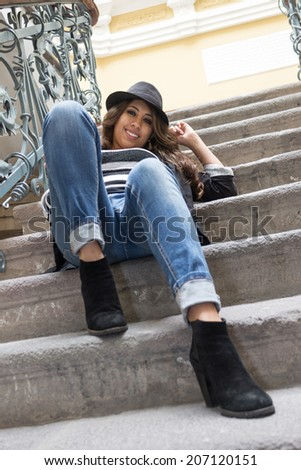 young woman wearing a black hat sitting on stairs smiling