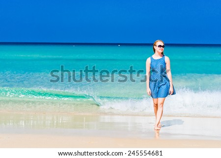 Young woman wearing a blue dress and sunglasses walking on a beach and enjoying the sun