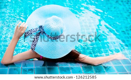 young woman wearing a blue hat sitting in the swimming pool - stock photo