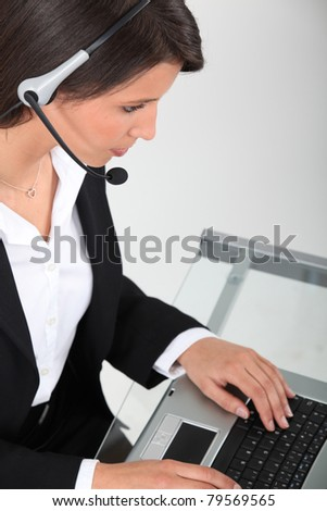 Young woman wearing a headset typing at a keyboard - stock photo