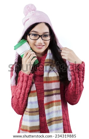 Young woman wearing a knitted winter jumper and holding a cup of hot drink in the studio - stock photo
