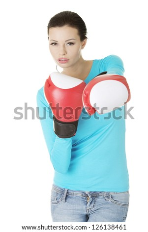 Young woman wearing a pair of boxing gloves. Woman ready for fight with problems concept.