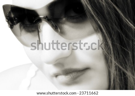Young woman wearing a pair of sunglasses. High-key closeup.