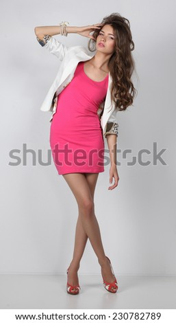 Young woman wearing a pink dress standing, isolated - stock photo