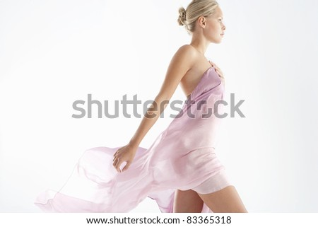 Young woman wearing a pink sarong which is flying in the wind.
