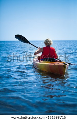 Young Woman Wearing a Safety Vest Heading out to sea Alone on Calm Water - stock photo