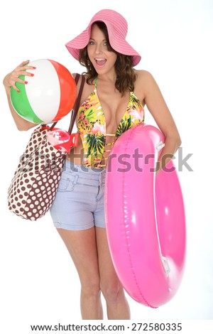 Young Woman Wearing a Swim Suit on Holiday Carrying a Beach Ball and Rubber Ring - stock photo