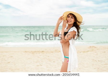 Young woman wearing a white dress and hat standing on a beach and enjoying the sun. - stock photo