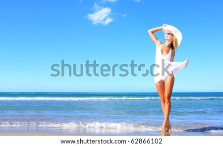 Young woman wearing a white dress and hat standing on a beach and enjoying the sun - stock photo