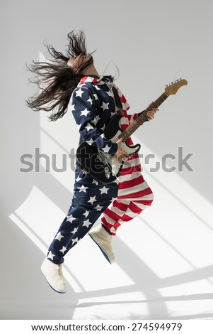 Young woman wearing American Flag pajamas playing guitar and celebrating Independence Day posing in studio - stock photo