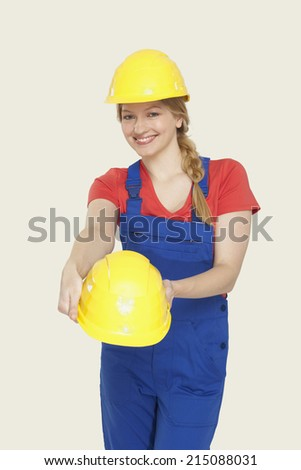 Young woman wearing and holding hardhats smiling - stock photo