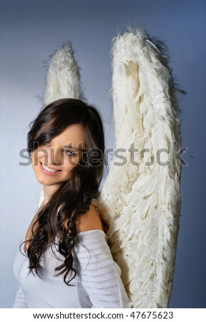 Young woman wearing angel wings smiling