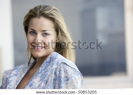 Young woman wearing bathrobe outdoors, portrait
