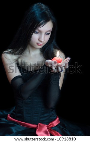 Young woman wearing black dress holding red candle over black background - stock photo
