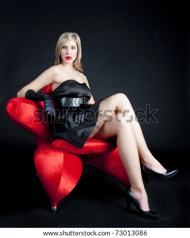young woman wearing black dress sitting in armchair - stock photo