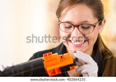 Young woman wearing black shirt performing toner change and printer maintenance, positive attitude smiling.