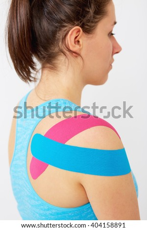 Young woman wearing blue and pink kinesio therapy tape on her shoulder - stock photo