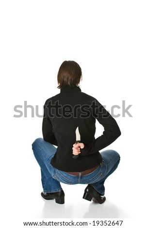 Young woman wearing blue jeans and a black jacket crouches and holds a knife behind her back. Isolated on a white background. - stock photo