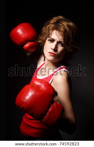 young woman wearing boxing gloves - stock photo