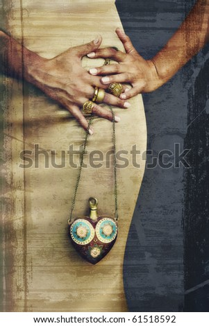 young woman wearing 22 carat yellow gold rings and holding antique heart shaped flask on grunge background - stock photo