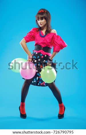 Young woman wearing colorful old-fashion clothes in pinup style
