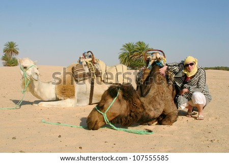 Young woman wearing desert clothes with camels in Sahara