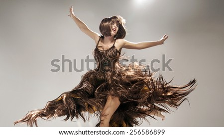 Young woman wearing dress made of hair - stock photo