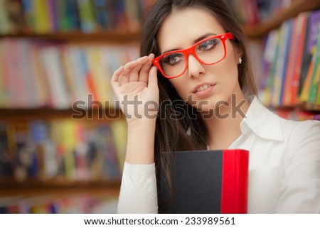 Young Woman Wearing  Glasses and Holding a Book - Portrait of a woman with red eyeglasses holding a book in a library  - stock photo