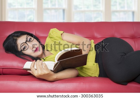 Young woman wearing glasses and lying on the sofa while holding and reading a books in the home