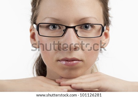 Young woman wearing glasses based her head on her hands - stock photo