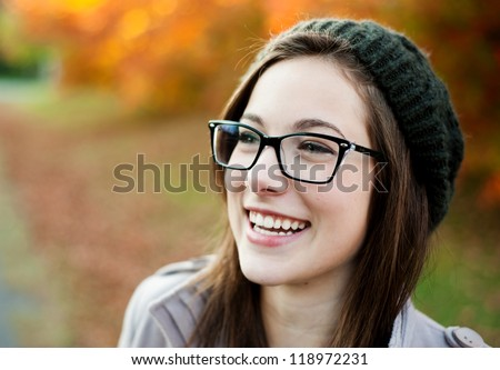 Young woman wearing glasses laughing in the fall