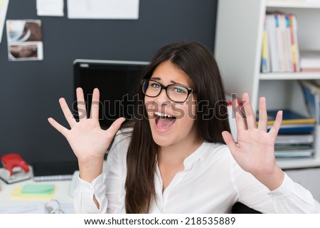 Young woman wearing glasses sitting at her desk in the office screaming in fear and raising her hands as if to ward off danger - stock photo