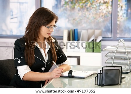 Young woman wearing glasses sitting at office desk, working. - stock photo