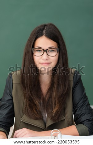 Young woman wearing glasses sitting in class at a desk with her back to the blackboard smiling at the camera - stock photo
