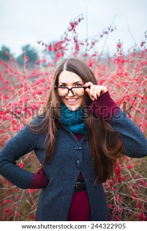 Young woman wearing glasses smiling in the fall