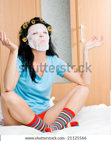 young woman wearing hair curlers and a mask sitting on the bed at home - stock photo