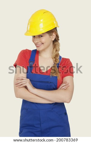 Young woman wearing hard hat smiling - stock photo