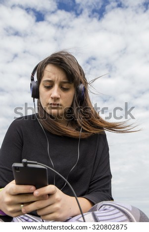 Young woman wearing headphones, using her cell phone, sky as background