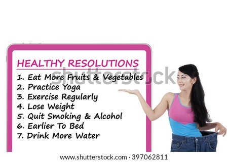 Young woman wearing her old jeans and showing the list of healthy resolutions on the board - stock photo