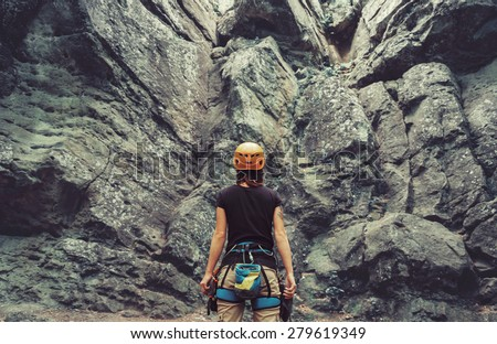Young woman wearing in climbing equipment standing in front of a stone rock outdoor and preparing to climb, rear view - stock photo