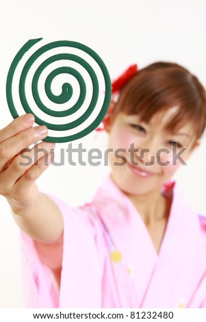 Young woman wearing Japanese kimono with mosquito coil - stock photo