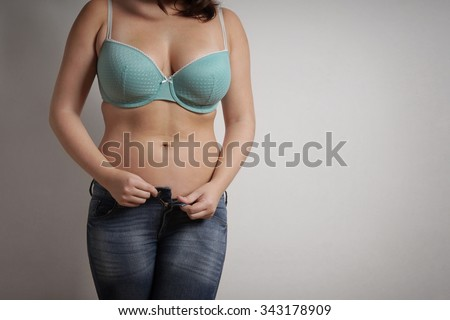 young woman wearing jeans and bra taking off her clothes                                - stock photo
